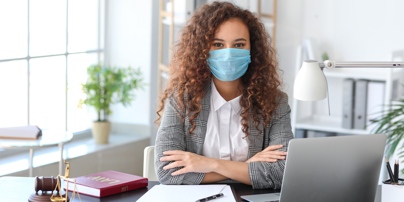 Female professional wearing a protective mask while back in the office