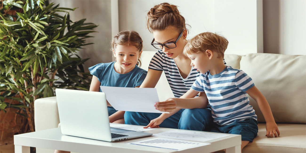 Busy woman working from home with kids sitting nearby