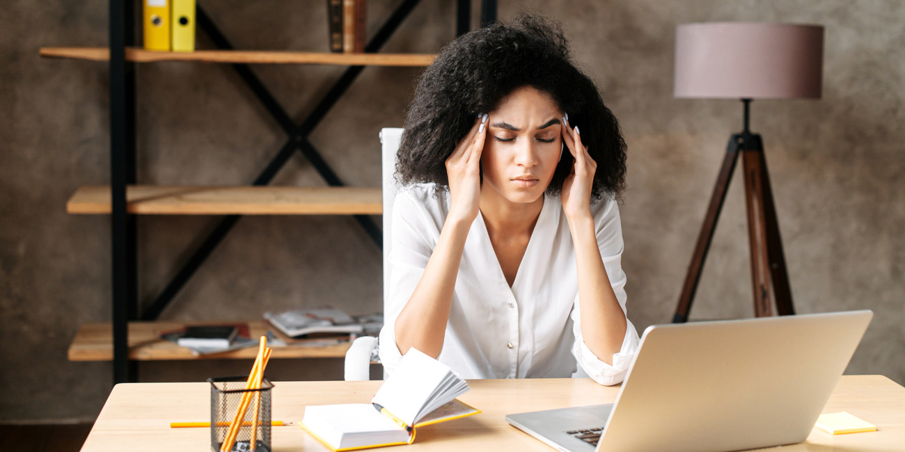 Woman rubbing her temples at work may be experience stress due to burnout