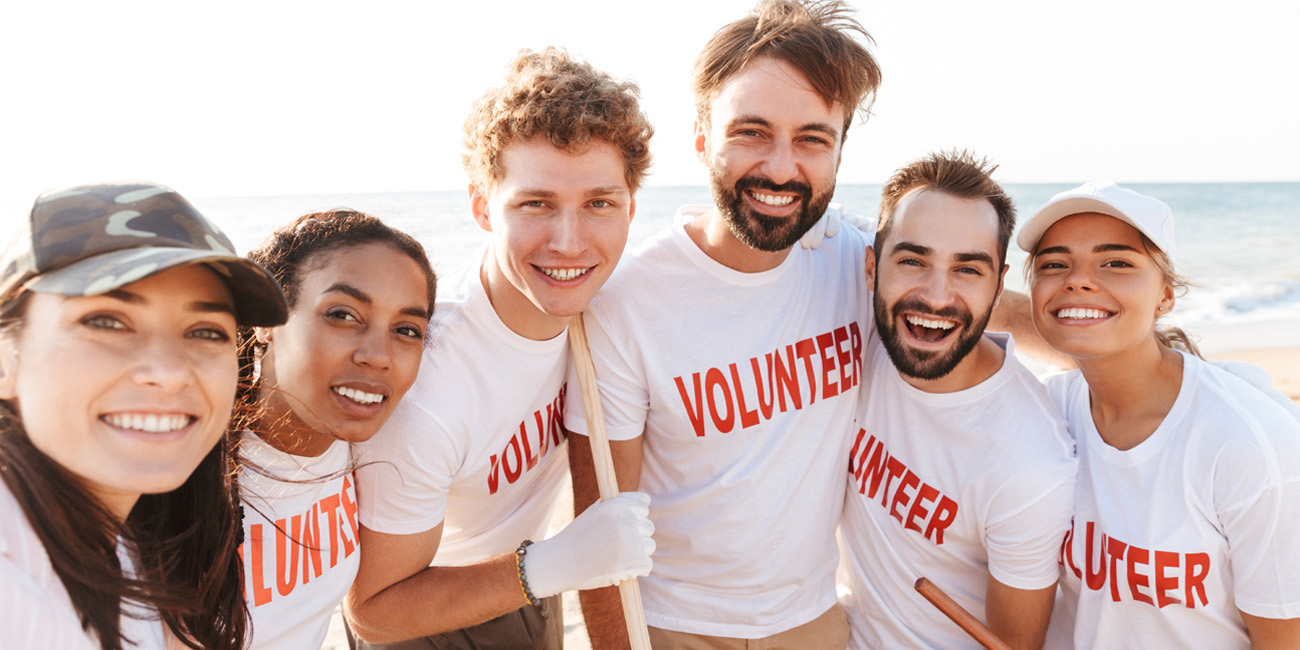 Volunteers smiling together while cleaning up a beach