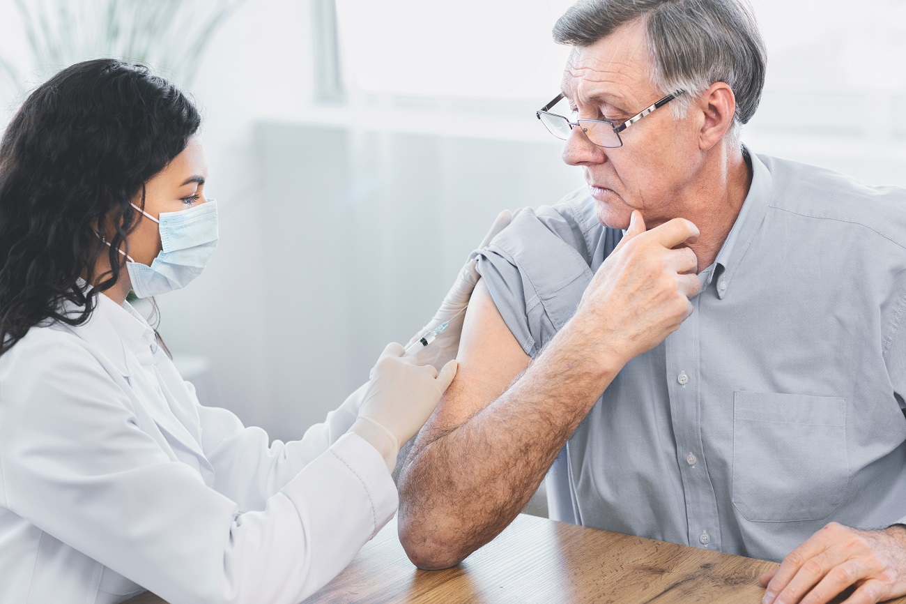 An elderly man is receiving his flu vaccination from his doctor