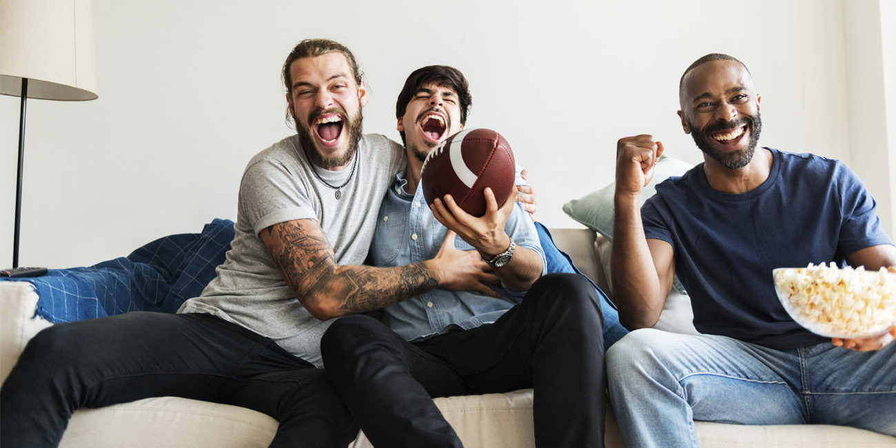 Three coworkers watching a football game at home