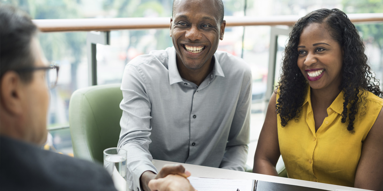 Young African American couple meeting with financial advisor to plan retirement